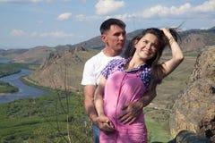 Junge Paare, die in den Bergen umarmen Stockfotografie