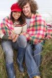 Junge Paare, die in den Sanddünen sitzen Lizenzfreie Stockfotografie