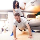 Junge Paare, die den Spaß zu Hause tut Gymnastik haben lizenzfreie stockfotos