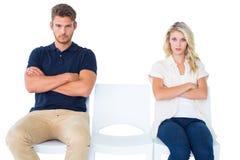 Junge Paare, die in den Stühlen sprechen nicht während des Arguments sitzen Lizenzfreie Stockfotos