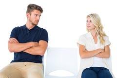 Junge Paare, die in den Stühlen sprechen nicht während des Arguments sitzen Stockfotografie