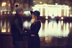 Junge Paare, die an der Abendstadt gehen Stockbilder