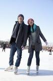 Junge Paare, die an der Eisbahn eislaufen Lizenzfreies Stockfoto