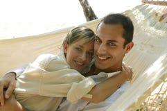 Junge Paare, die in der Hängematte liegen lizenzfreies stockfoto