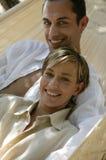 Junge Paare, die in der Hängematte liegen Stockfotografie