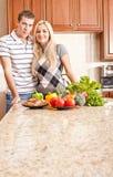 Junge Paare, die in der Küche aufwerfen Stockbild