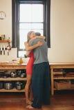 Junge Paare, die in der Küche sich umfassen Lizenzfreies Stockbild