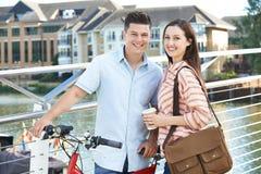 Junge Paare, die in der städtischen Landschaft arbeiten gehen und radfahren Stockbilder