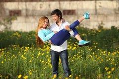 Junge Paare, die in der Wiese stehen Lizenzfreie Stockfotografie