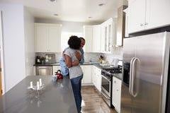 Junge Paare, die in der Wohnungs-Küche umarmen Stockbild