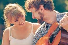 Junge Paare, die die Gitarre spielend im Freien kampieren Stockfotografie