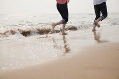 Junge Paare, die in die Wellen laufen Lizenzfreies Stockbild