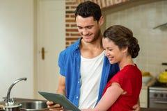 Junge Paare, die digitale Tablette betrachten Stockbild