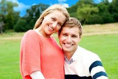 Junge Paare, die draußen auf grünem Gras sitzen Lizenzfreies Stockbild