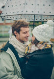 Junge Paare, die draußen herein unter Regenschirm umfassen Stockbilder