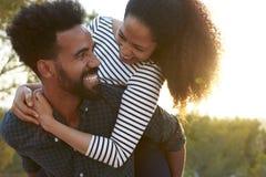Junge Paare, die draußen huckepack tragen, Haupt- und Schultern lizenzfreies stockbild