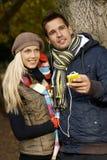 Junge Paare, die draußen lächelnde Musik hören Stockfoto