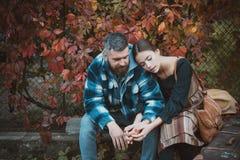 Junge Paare, die draußen am Park am schönen Herbsttag sitzen Abenteuer, Reise, Tourismus, Wanderung und Leutekonzept - stockfotografie