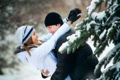 Junge Paare, die draußen spielen. Winterjahreszeit. Stockfoto
