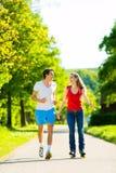 Junge Paare, die draußen Sport tun Stockbild