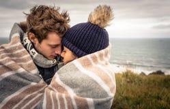 Junge Paare, die draußen unter Decke in a umfassen stockbild