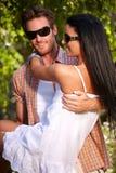Junge Paare, die draußen lächeln umfassen Stockfotos