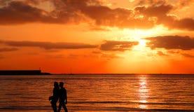 Junge Paare, die durch das Meer bei Sonnenuntergang gehen Stockbilder