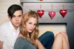 Junge Paare, die durch den Kamin sitzen Lizenzfreies Stockfoto