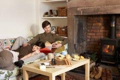 Junge Paare, die durch Feuer sich entspannen Stockbilder