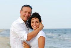 Junge Paare, die durch Meer umfassen Stockfotos