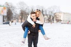 Junge Paare, die durch die Stadt gehen Der Kerl trägt das Mädchen stockbild
