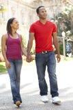 Junge Paare, die durch Stadt-Straße gehen Stockfotos