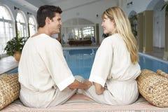 Junge Paare, die durch Swimmingpool sich entspannen Stockfoto