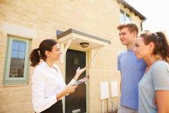 Junge Paare, die ein Haus mit weiblicher Immobilienagentur ansehen
