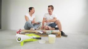 Junge Paare, die in ein neues Haus sich bewegen Frau und Ehemann, die eine Farbe für eine Wand vorwählen stock footage