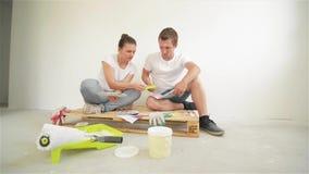 Junge Paare, die in ein neues Haus sich bewegen Frau und Ehemann, die eine Farbe für eine Wand vorwählen stock video
