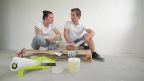 Junge Paare, die in ein neues Haus sich bewegen Frau und Ehemann, die eine Farbe für eine Wand vorwählen stock video footage