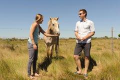 Junge Paare, die ein Pferd einziehen Stockfotos