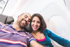 Junge Paare, die ein selfie auf dem Flugzeug nehmen stockfotografie