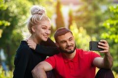 Junge Paare, die ein selfie mit intelligentem Telefon nehmen Lizenzfreies Stockbild