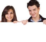 Junge Paare, die ein Zeichen anhalten Lizenzfreie Stockbilder