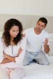 Junge Paare, die eine Debatte auf dem Bett haben Lizenzfreie Stockfotos