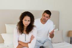 Junge Paare, die eine Debatte auf dem Bett haben Stockfotos
