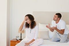 Junge Paare, die eine Debatte auf dem Bett haben Stockbild