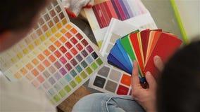 Junge Paare, die eine Farbe für eine Eigentumswohnung, Nahaufnahme vorwählen stock footage
