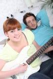 Junge Paare, die eine Gitarre spielen Lizenzfreie Stockfotografie
