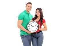 Junge Paare, die eine große Wanduhr halten Stockbilder
