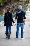 Junge Paare, die in eine Park-Holding-Hände gehen Lizenzfreies Stockfoto