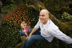 Junge Paare, die in einem Baum spielen Lizenzfreie Stockfotos