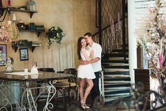 Junge Paare, die in einem Café umfassen lizenzfreie stockfotografie
